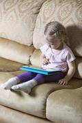 Girl using digital tablet on sofa Stock Photos