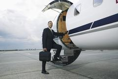 Businessman boarding a private airplane - stock photo