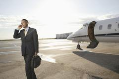 Businessman with cell phone standing near a private airplane - stock photo