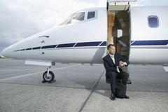 Businessman sitting on a private airplane's steps - stock photo