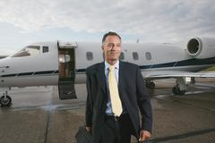Businessman in front a private airplane - stock photo