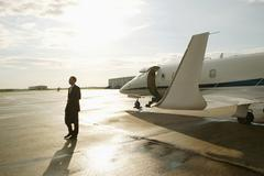 Businessman disembarking from a private airplane - stock photo