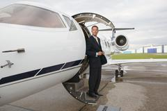 Businessman standing on a private airplane's steps - stock photo