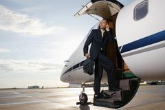 Businessman standing on a private airplane's steps Stock Photos
