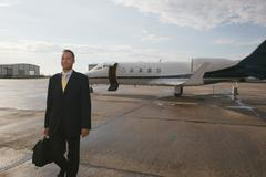 Businessman standing in front of a private airplane - stock photo