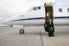 Businessman sitting on a private airplane's steps Stock Photos