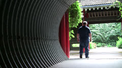 OVERWEIGHT MAN COMING AND GOING IN CORRUGATED TUNNEL - stock footage