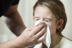 Father wiping daughter's nose with tissue Stock Photos