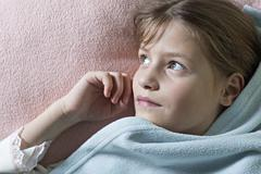 Daydreaming girl under blanket - stock photo