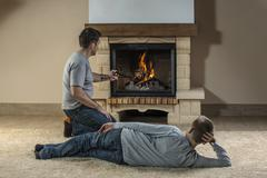 Stock Photo of Father and son relaxing next to fire