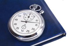 stopwatch and the notebook on a white background - stock photo