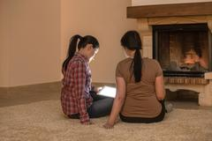 Stock Photo of Two women relaxing next to fire and looking at digital tablet