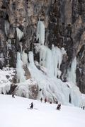 Skiers observe ice climber on rock face at Lagazuoi, South Tyrol, Italy - stock photo
