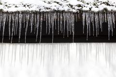 Snow and a row of icicles hanging from the eaves of a building Stock Photos