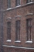The exterior of a brick building during a blizzard Stock Photos