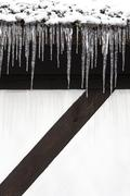 Snow and a row of icicles hanging from the eaves of a building - stock photo