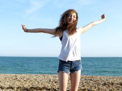 A cheerful teengirl standing on the beach with her arms raised in exhilaration Stock Photos