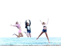 Three friends jumping in excitement on the beach Stock Photos