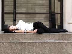 Stock Photo of A young sleeping businessman lying on steps outside a building