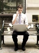 Businessman using a smart phone while using a laptop and sitting on bench with Stock Photos