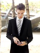 A serious young businessman text messaging on his smart phone - stock photo