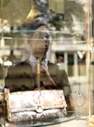 A young businessman adjusting his tie using a shop window as a mirror Stock Photos