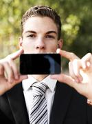 A young businessman holding his smart phone up in front of his mouth - stock photo