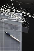 A cutting mat with shredded paper, ruler and utility knife on black background Stock Photos