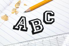 Varsity font stickers spelling out A, B, C atop a lined paper notebook with Stock Photos