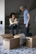 A mixed couple packing moving boxes Stock Photos