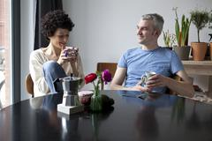 A cheerful hip mixed couple enjoying breakfast together in their dining room Stock Photos