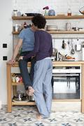A mixed couple kissing in their kitchen Stock Photos