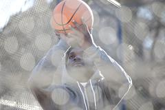 A hip young man aiming a basketball while on an outdoor basketball court Stock Photos
