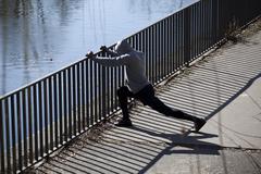 Mies tekee venyttely syöksy vastaan kaide lähellä jokea Kuvituskuvat