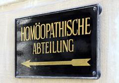 Metal plaque reading 'Homeopathic department' in German Stock Photos