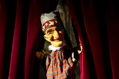 Punch from the classic puppet show Punch and Judy parting the curtains on stage - stock photo