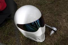 A sleek modern crash helmet lying on grass next to socket wrench Stock Photos