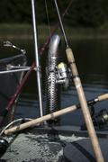 An arrangement of various fishing rods on a lake jetty Stock Photos