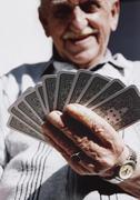 Vanhempi mies, jolla pelikortit Kuvituskuvat