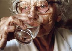 Senior woman drinking a glass of water Stock Photos