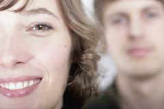 Close up of a young woman with a man blurred in the background - stock photo