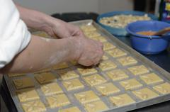 A baker's hands arranging almonds on cookie dough - stock photo