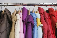 Numerous colorful jackets on a rack - stock photo
