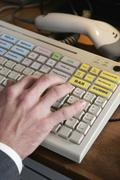 High angle view of a man operating a keyboard in at a checkout counter Stock Photos