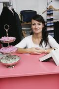 A woman sitting at a cash register in a clothing store Stock Photos