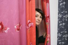 A woman looking through the curtains of a changing room - stock photo