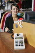 A woman sitting at the cash register of a clothing store, smiling Stock Photos
