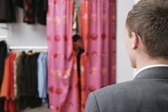 Rear view of a man looking at a woman behind the curtains of a changing room - stock photo