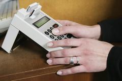 A woman operating a credit card machine Stock Photos