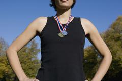 Front view of a young woman wearing gold and silver medals - stock photo
